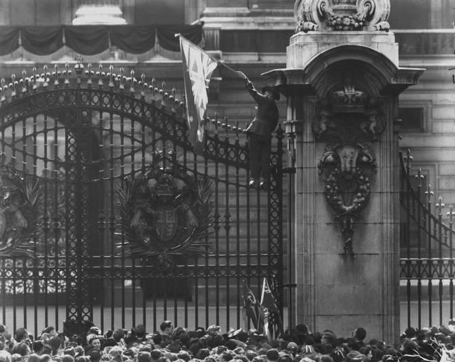 An Australian soldier climbs the gates of Buckingham Palace