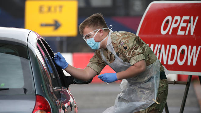 A soldier from 2 Scots Royal Regiment of Scotland take a test sample at a Covid-19 testing centre at Glasgow Airport