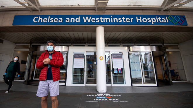 File photo: A man and woman wearing face masks outside the Chelsea and Westminster Hospital in London