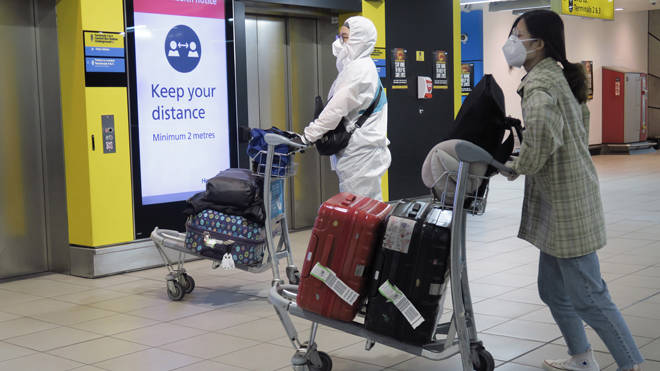 Air passengers in protective gear at Heathrow Airport