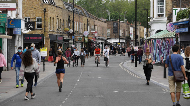 People walk and cycle through Broadway Market in London, as the UK continues in lockdown