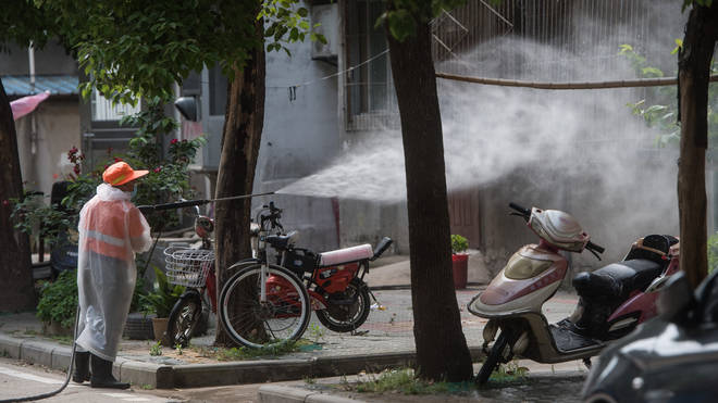 A staff member disinfects the Sanmin residential community in Dongxihu District of Wuhan