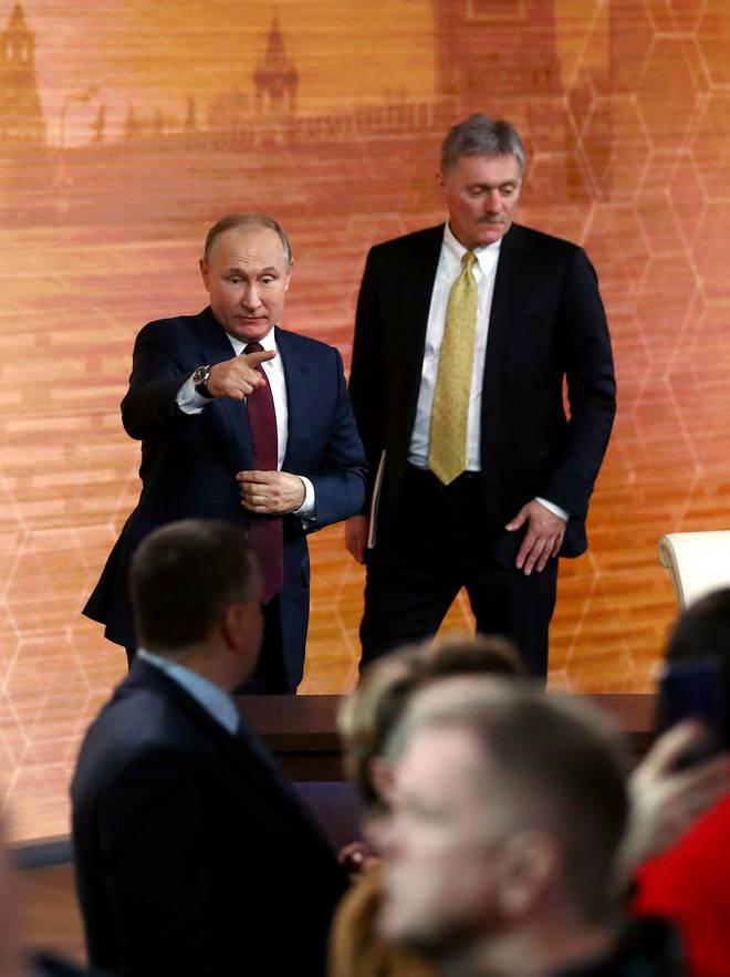 Russia's President Vladimir Putin (L) and his spokesman Dmitry Peskov