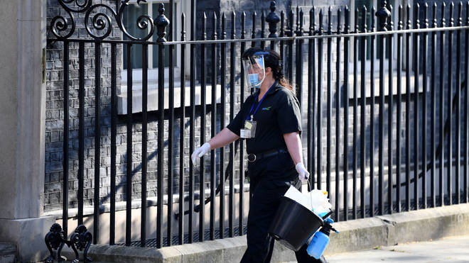 A cleaner in PPE is seen arriving at Downing Street on 16 April