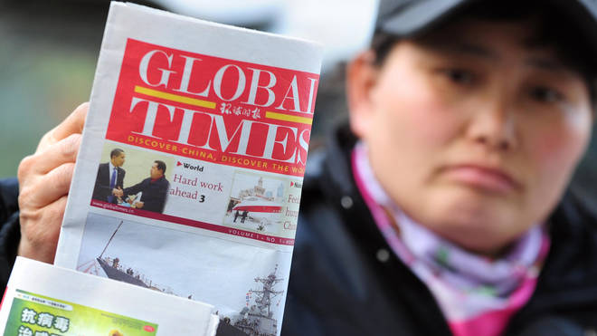 File photo from 2009 showing a news vendor displaying the Global Times on her stand