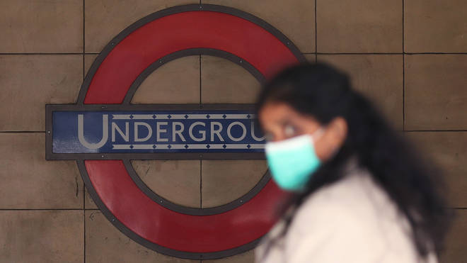 File photo: A woman wearing a face mask walks past Leicester Square Underground station
