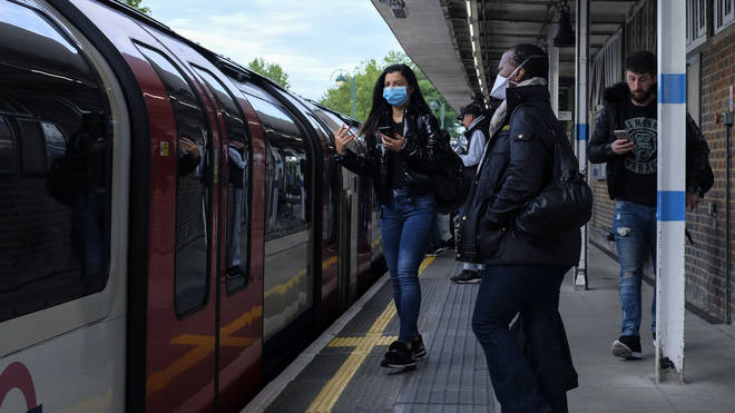 Commuters board Tube trains in protective masks