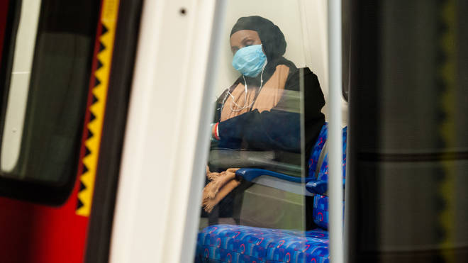 A woman pictured on the Tube in a protective face mask