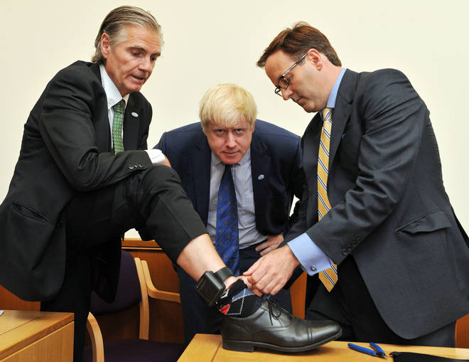 File photo of a sobriety tag being removed as Boris Johnson, at the time the Mayor of London, looks on