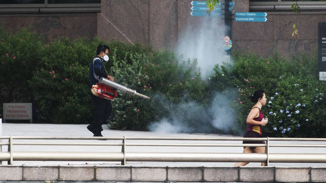 Workers spraying pesticides in Singapore as part of the fight against dengue fever