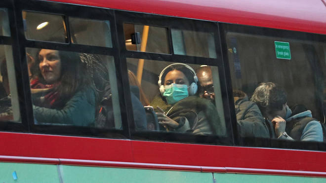 A woman wears a protective face mask on a London bus