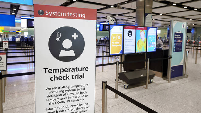 Signs informing of temperature screening equipment being trialled at London Heathrow Airport