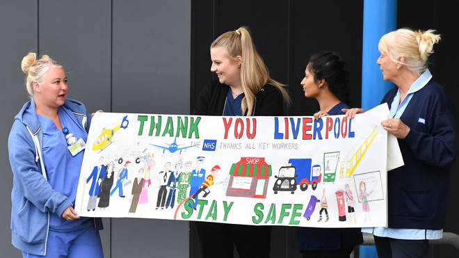 "NHS workers hold up a sign thanking Liverpool ahead of a national ""clap for carers"""