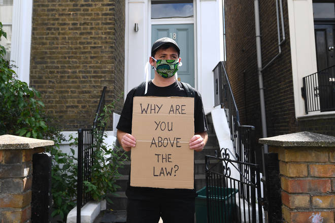 An activist stands outside Dominic Cummings' house in protest