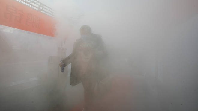 A resident walks through a temporary room of disinfectant spray to return home in north China