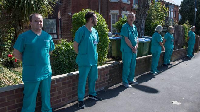 Hospital staff line the streets