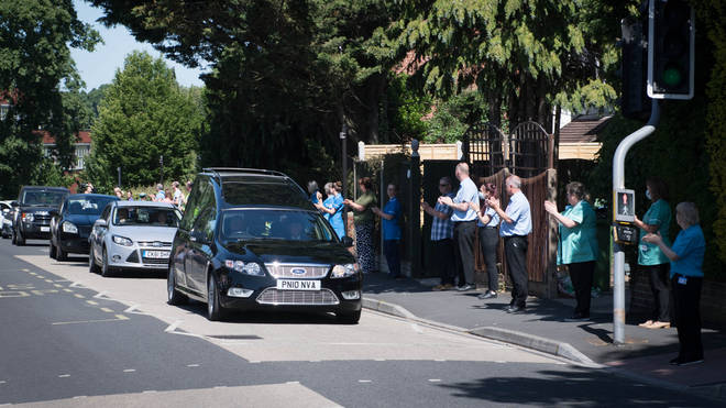 NHS staff and passersby broke into applause as the cortage passed by