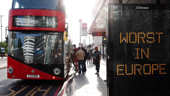 People board a bus at a stop bearing the message 'Worst In Europe'on Westminster Bridge Road in London
