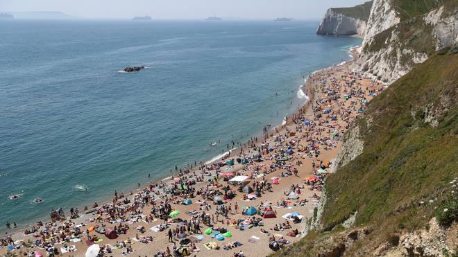 People enjoying the good weather on the beach at Durdle Door, near Lulworth in Dorset