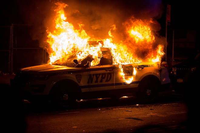 An NYPD vehicle burns as violence intensifys