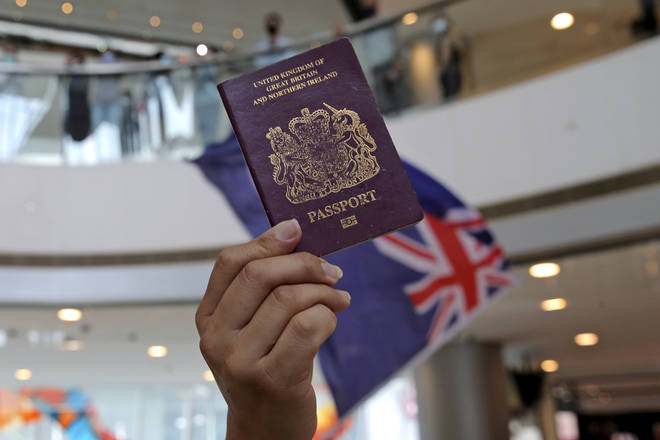 Protesters hold a British National (Overseas) passport and Hong Kong colonial flag in a shopping mall during a protest against China's national security legislation for the city, in Hong Kong