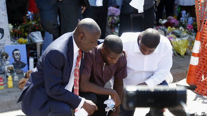 Mr Floyd's son Quincy Mason (centre) kneels with his uncle Twain Mason (right) and family lawyer Ben Crump (left) at a memorial site