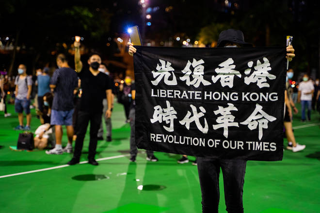 "Protesters held signs saying ""Liberate Hong Kong"" and ""Revolution Of Our Times"""