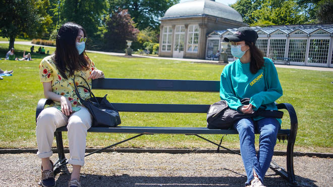 Two friends wearing face masks sit on a bench as they maintain social distancing at the Botanical Gardens , Sheffield
