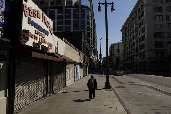 A man walks on a sidewalk lined with shuttered shops in Los Angeles