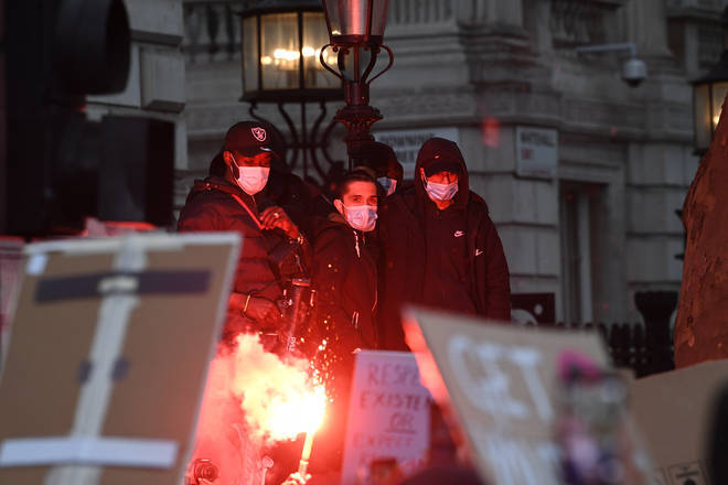 Protesters lit flares as the crowd gathered on Whitehall