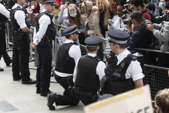 Two officers kneel down in front of protesters at Downing Street