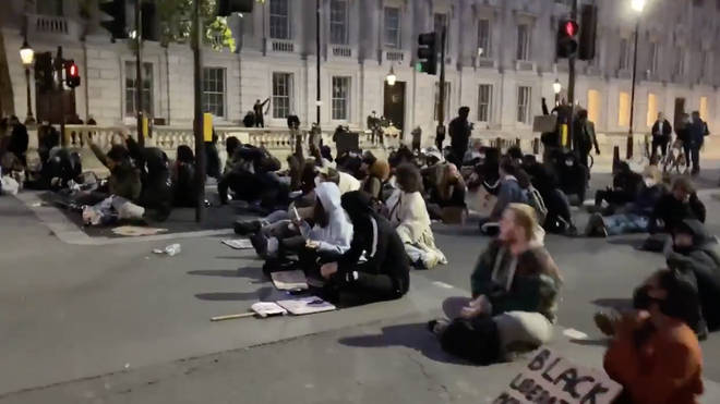 "A small group of protesters sat in central London into the evening, singing: ""Where is the Love"""