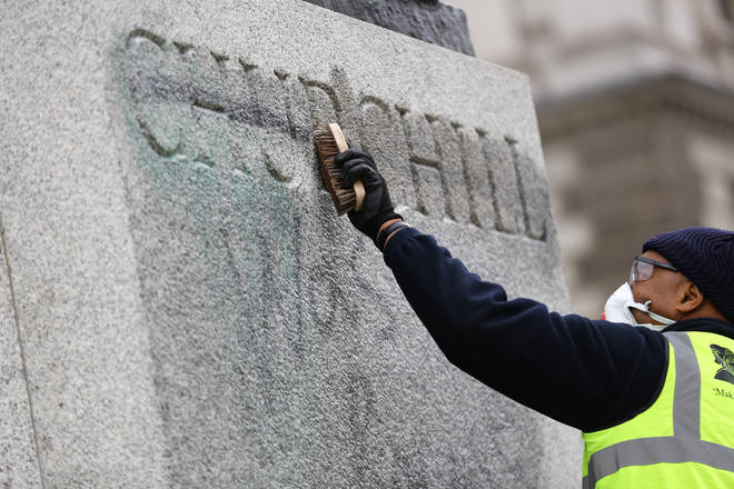 Volunteers clean graffiti which was sprayed on a statue for Winston Churchill