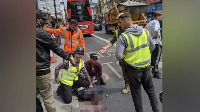 Workmen hold down a suspect knifeman