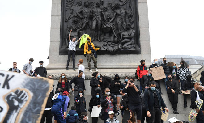Protestors stood on a monument holding placards