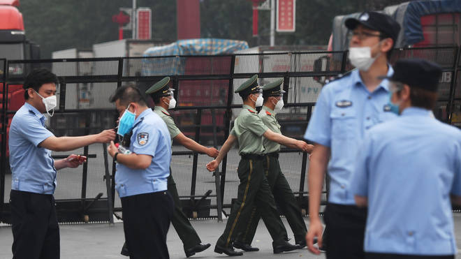 Paramilitary police officers march as police stand guard at the entrance to the closed Xinfadi market in Beijing