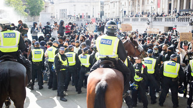 A line of riot police and protesters in London today