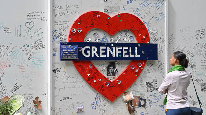 A woman reads messages of support written on the wall surrounding Grenfell tower
