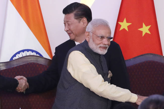 File photo: Indian Prime Minister Narendra Modi, front and Chinese President Xi Jinping shake hands with leaders at the BRICS summit in Goa
