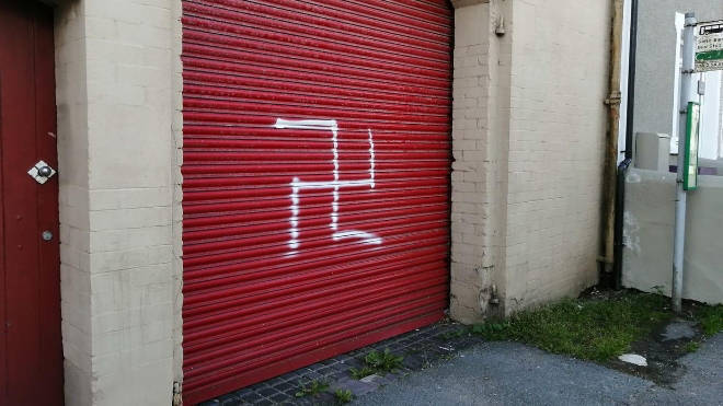 A man has been arrested after a swastika was painted on a black family's home