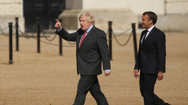 Prime Minister Boris Johnson and French president Emmanuel Macron walk together at Horse Guards Parade to watch the display