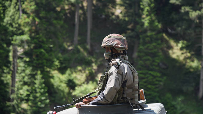 Indian army man keeps vigil from top of armored vehicle as they moves on national Highway leading towards Ladakh