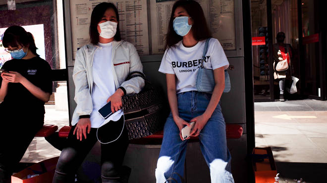 Two women pictured shopping in face masks in London as it was announced the covid-19 threat level is being reduced
