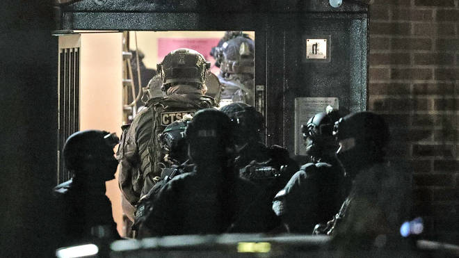 Counter terrorism officers are seen at a nearby address