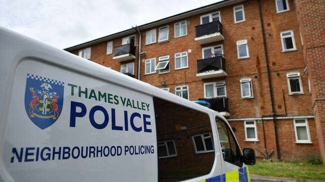 A police van is pictured outside a block of flats where the suspect of a multiple stabbing incident the previous day is believed to have lived