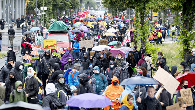People in protective masks march at a protest in Berlin