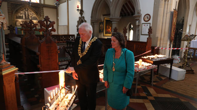Wokingham Town Mayor Tony Lack and wife Claire light a candle in St Paul's Parish Church, Wokingham, for teacher James Furlong
