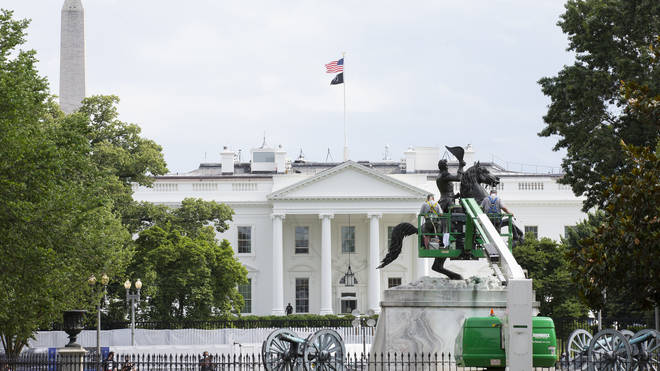 Workers clean the Andrew Jackson statue in Lafayette Square near the White House in Washington D.C
