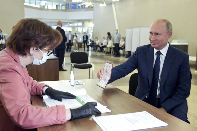 Mr Putin showed his passport to an election worker at the polling station