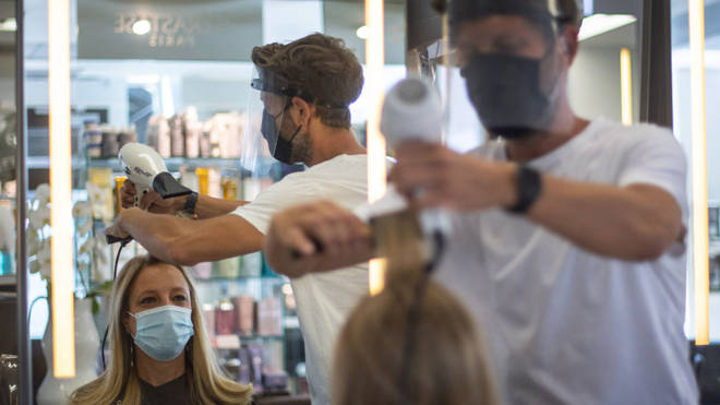 A hairdresser in PPE at work